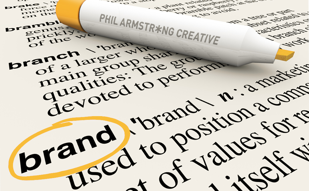 Phil Armstrong Creative's orange marker pen encircles the word Brand in a dictionary.